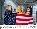Cheerful female friends enfolded in american flag 38351599