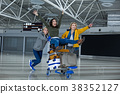 Glad tourists wheeling on luggage trolley 38352127