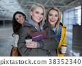 glad females holding beverage and notebooks 38352340