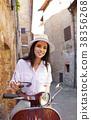 Young beautiful italian woman sitting on a italian scooter. 38356268
