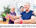 Physio showing senior couple how to use rubber 38370114