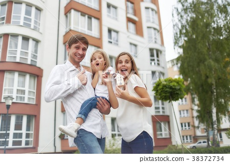 Happy family in front of new apartment building 38372734