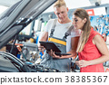 Auto mechanic showing to a customer the engine 38385367