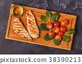 Fried chicken breast on a serving board. 38390213