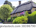 stone house in village with flying British flag 38396790