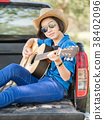 Woman wear hat and playing guitar on pickup truck 38402096