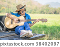 Woman wear hat and playing guitar on pickup truck 38402097
