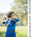 Woman wear hat and carry her guitar in grass field 38402098