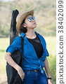 woman wear hat walking and carry her guitar bag 38402099