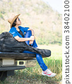 Woman wear hat and carry her guitar bag on pickup truck 38402100