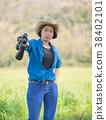 Woman wear hat and hold binocular in grass field 38402101