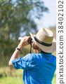 Woman wear hat and hold binocular in grass field 38402102