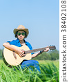 Women short hair wear hat and sunglasses sit playing guitar in g 38402108