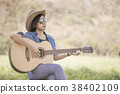 Women short hair wear hat and sunglasses sit playing guitar in g 38402109