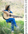 Women short hair wear hat and sunglasses sit playing guitar in g 38402110