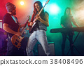 Rock band performs on stage. Guitarist, bass guitar and drums. 38408496