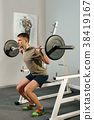 Athletic man doing squats exercise with dumbbell 38419167