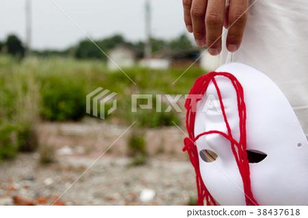 一個人放下手中的白色面具和紅色毛線 38437618
