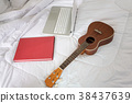 Practice playing ukulele on bed in the morning. 38437639