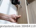A man is installing a hook. 38464110
