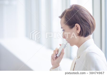 Short-haired woman smoking a heated cigarette 38474967