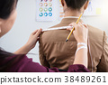 Young woman dressmaker or designer working as measuring for clot 38489261