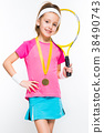 Cute little girl with tennis racket and medal in 38490743