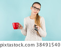 Attractive woman with ponytail and cup with remote 38491540