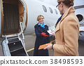 Lady giving document to beaming stewardess 38498593