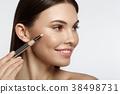 Cheerful girl applying tone cream 38498731