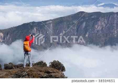 hiker taking selfie on mountain peak cliff edge 38504651