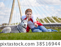 Girl playing with her  dog in city park 38516944