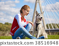 Girl playing with her  dog in city park 38516948