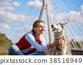 Girl playing with her  dog in city park 38516949