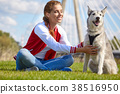 Girl playing with her  dog in city park 38516950