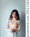 Happy beautiful woman holding festive sparkler 38521582