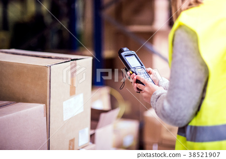 Warehouse woman worker with barcode scanner. 38521907