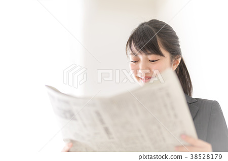 A woman reading a newspaper 38528179