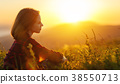 Woman sits with her back in the field and look sunset in the mou 38550713