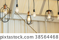 Close up of the lamp hanging from a ceiling. 38564468