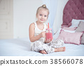 Little blonde girl sitting on the bed reading a 38566078