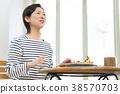 หญิงสาววัยห้าสิบกำลังรับประทานแพนเค้กในร้านกาแฟ 38570703