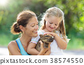 Kids and farm animals. Child with baby pig at zoo. 38574550