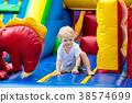 Child jumping on playground trampoline. Kids jump. 38574699