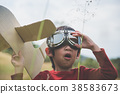 child playing cardboard airplane in the grass  38583673