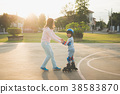 Mother helping her son to playing roller skate 38583870