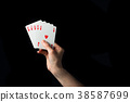 Playing cards in hand isolated on black background 38587699