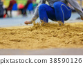 Sportsman landing into sandpit in long jump 38590126
