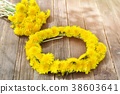 Wreath of dandelions on a wooden table. Summer 38603641