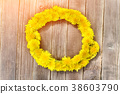 Wreath of dandelions on a wooden table. Summer 38603790